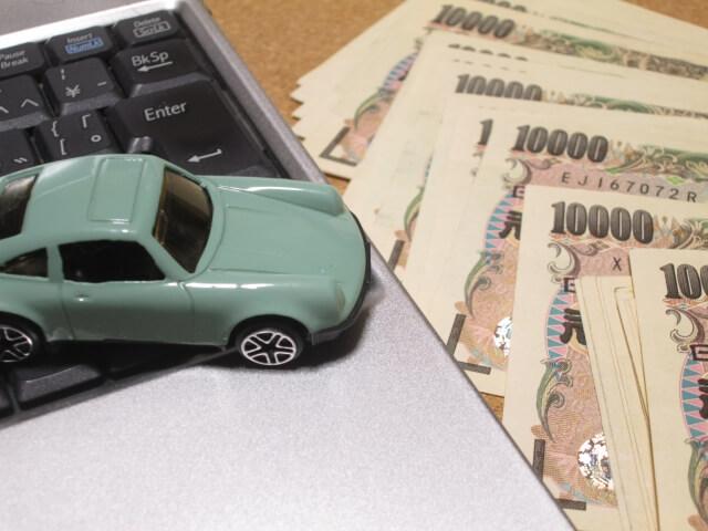 パソコンの上に置かれたおもちゃの車とお金