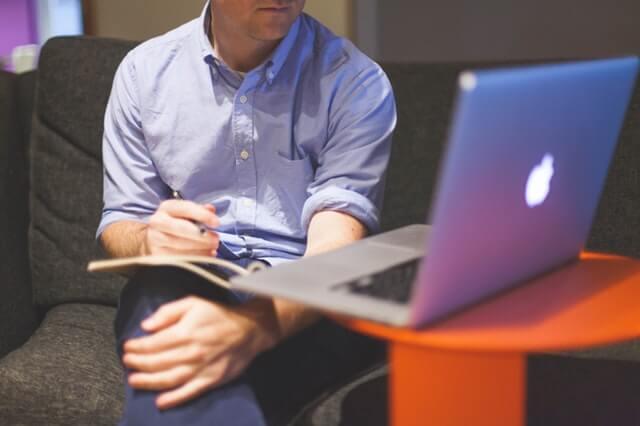 パソコンを見ながらメモをする男性