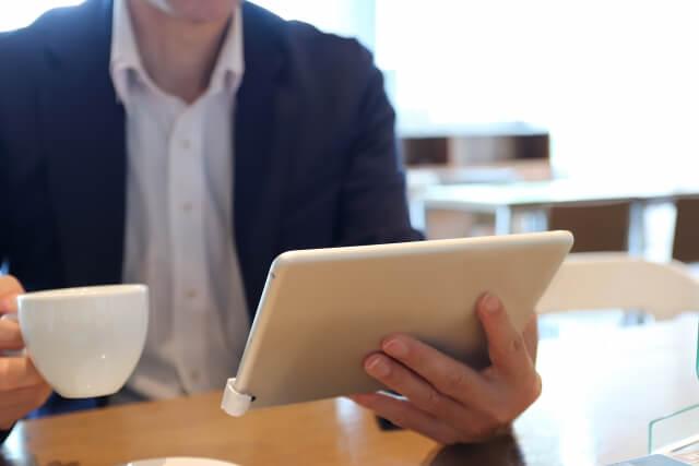 コーヒー片手にタブレットを見る男性