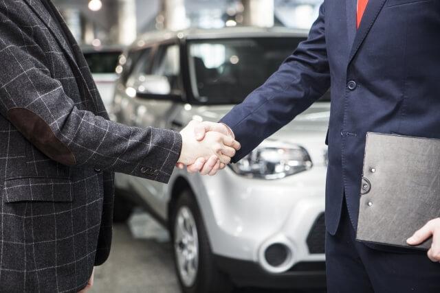 車の前握手する男性