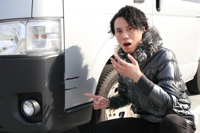 傷が入った車を見る男性