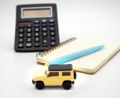 並べられた車のおもちゃとノートと電卓