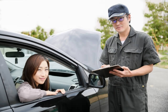 車に乗った女性と整備士